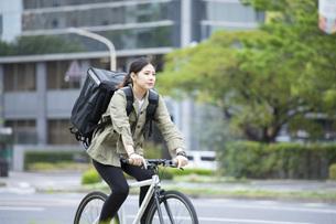 自転車で荷物の配送を行う若い女性の写真素材 [FYI04493644]