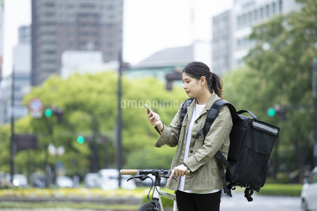 自転車で荷物の配送を行う若い女性の写真素材 [FYI04493652]
