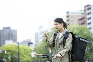 自転車で荷物の配送を行う若い女性の写真素材 [FYI04493653]