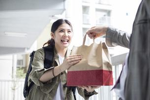 リュックを背負って荷物を届ける宅配サービスの写真素材 [FYI04493660]