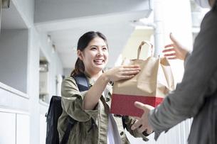 リュックを背負って荷物を届ける宅配サービスの写真素材 [FYI04493661]