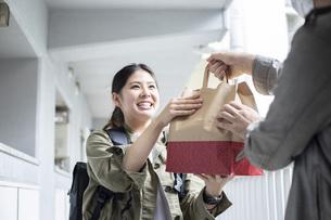 リュックを背負って荷物を届ける宅配サービスの写真素材 [FYI04493663]