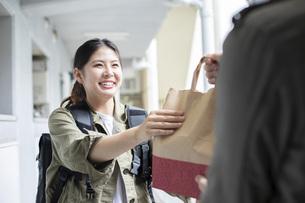 リュックを背負って荷物を届ける宅配サービスの写真素材 [FYI04493666]