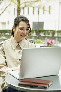 テラス席でパソコンを使う20代女性の写真素材 [FYI04494103]