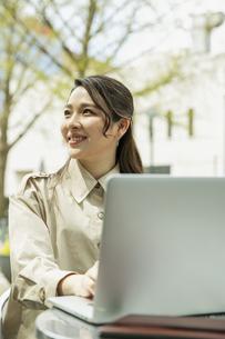 テラス席でパソコンを使う20代女性の写真素材 [FYI04494105]