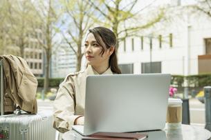 テラス席でパソコンを使う20代女性の写真素材 [FYI04494106]