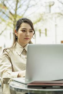 テラス席でパソコンを使う20代女性の写真素材 [FYI04494107]