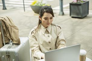 テラス席でパソコンを使う20代女性の写真素材 [FYI04494108]