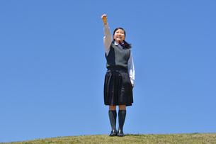 青空でガッツポーズをする女の子の写真素材 [FYI04494323]