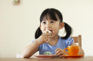 カップケーキを食べている女の子の写真素材 [FYI04494344]