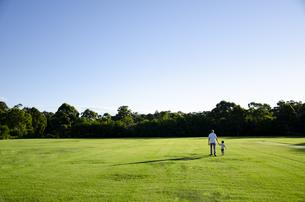 芝生の上を手を繋いで歩いている親子の写真素材 [FYI04494363]