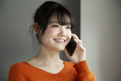 電話をする笑顔の20代女性の写真素材 [FYI04494455]