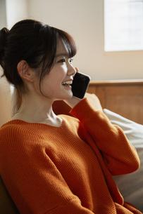 電話をする笑顔の20代女性の写真素材 [FYI04494460]