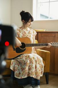 演奏する姿を撮る笑顔の20代女性の写真素材 [FYI04494478]