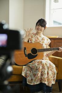 演奏する姿を撮る笑顔の20代女性の写真素材 [FYI04494480]