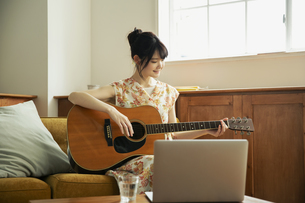 演奏する笑顔の20代女性の写真素材 [FYI04494482]