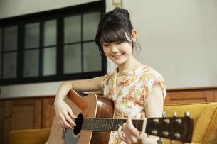 演奏する笑顔の20代女性の写真素材 [FYI04494486]