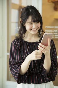 スマホを持つ笑顔の20代女性の写真素材 [FYI04494495]