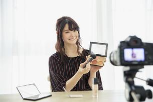 メイク動画の撮影をする笑顔の20代女性の写真素材 [FYI04494501]