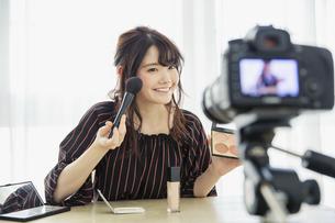 メイク動画の撮影をする笑顔の20代女性の写真素材 [FYI04494502]