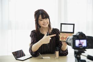 メイク動画の撮影をする笑顔の20代女性の写真素材 [FYI04494504]