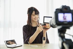 メイク動画の撮影をする笑顔の20代女性の写真素材 [FYI04494505]