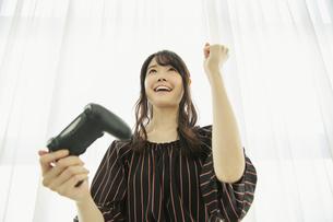 テレビゲームをする笑顔の20代女性の写真素材 [FYI04494517]
