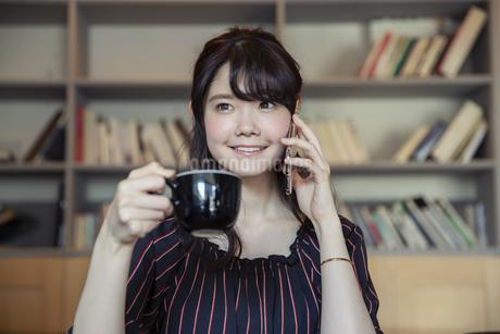 電話をする笑顔の20代女性の写真素材 [FYI04494525]