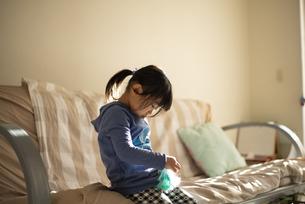 ソファに座って下を向いている女の子の写真素材 [FYI04495229]