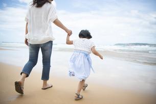 ビーチを歩いている親子の後ろ姿の写真素材 [FYI04495310]