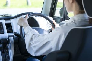 車のハンドルを握る若い女性の手元の写真素材 [FYI04495605]