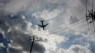 住宅街の上を低空で飛行するジェット旅客機の写真素材 [FYI04496370]