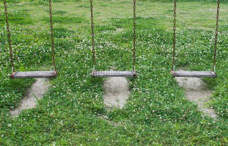 三つとも低い座面が木製のブランコの写真素材 [FYI04496489]