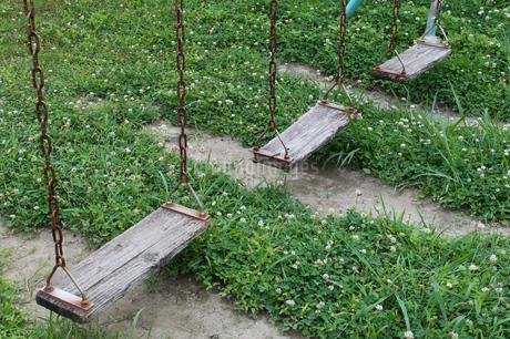 三つとも低い座面が木製のブランコの写真素材 [FYI04496491]