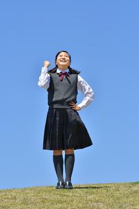 青空でガッツポーズをする女の子の写真素材 [FYI04496637]