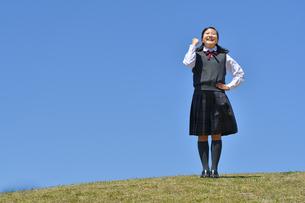 青空でガッツポーズをする女の子の写真素材 [FYI04496638]