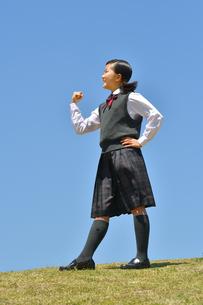 青空でガッツポーズをする女の子の写真素材 [FYI04496639]