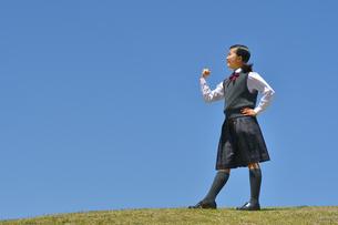 青空でガッツポーズをする女の子の写真素材 [FYI04496640]