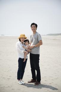 ビーチにいる3人家族の写真素材 [FYI04496659]