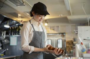 キッチンで働く20代女性の写真素材 [FYI04497523]