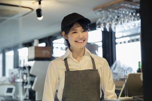 カフェで働く笑顔の20代女性の写真素材 [FYI04497524]
