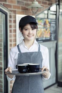 飲み物を提供する20代女性カフェ店員の写真素材 [FYI04497527]