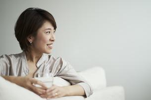 ソファでくつろぐ40代日本人女性の写真素材 [FYI04497856]