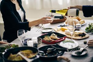 ホームパーティーでワインを注ぐの写真素材 [FYI04497857]