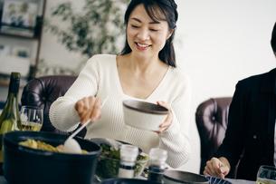 料理を取り分ける40代日本人女性の写真素材 [FYI04497861]