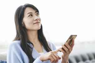 スマートフォンを操作する40代日本人女性の写真素材 [FYI04497904]