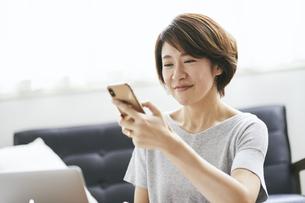 スマートフォンを見る40代日本人女性の写真素材 [FYI04497914]