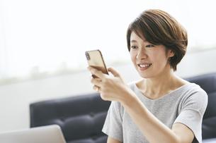 スマートフォンを見る40代日本人女性の写真素材 [FYI04497916]
