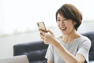 スマートフォンを見る40代日本人女性の写真素材 [FYI04497917]