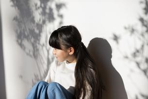 壁に寄り掛かる女の子の写真素材 [FYI04498055]